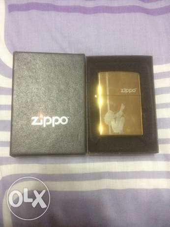 Gold Colored Zippo With A Stripper Logo For Sale المنيل -  2